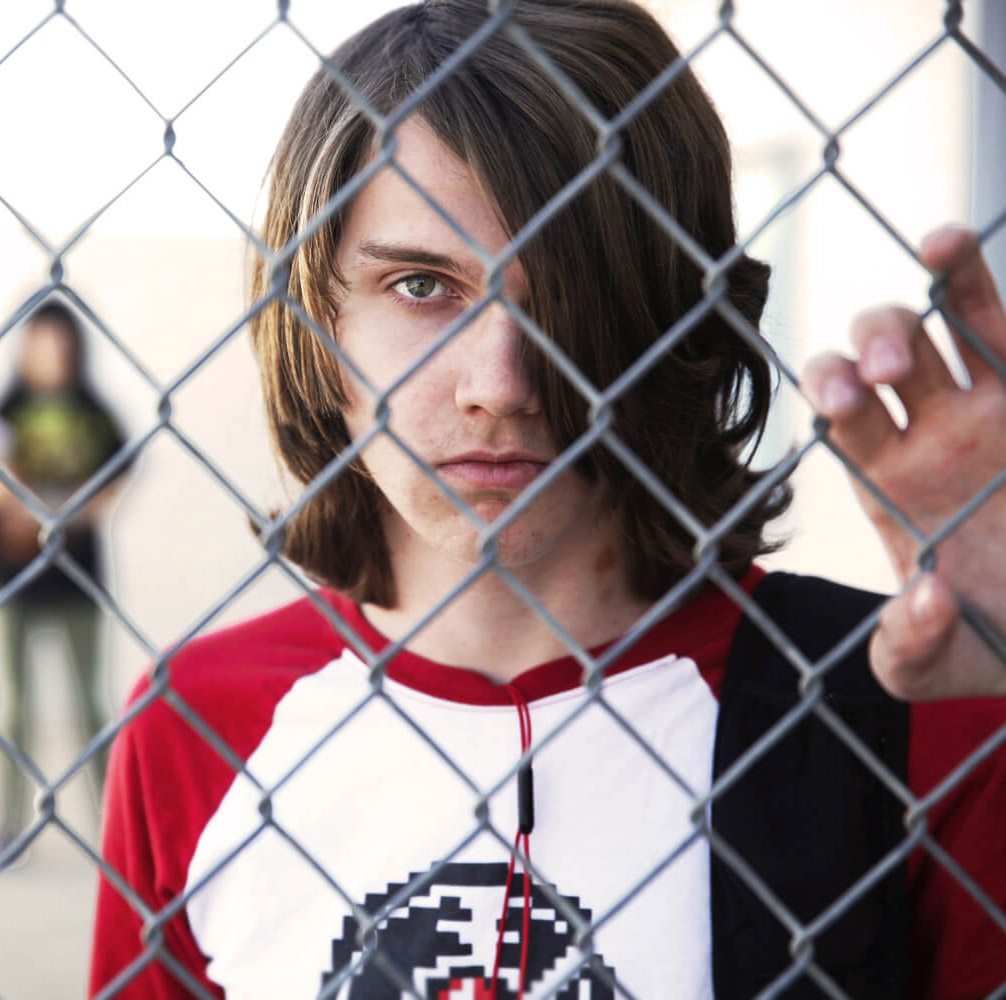 Teen looking through fence